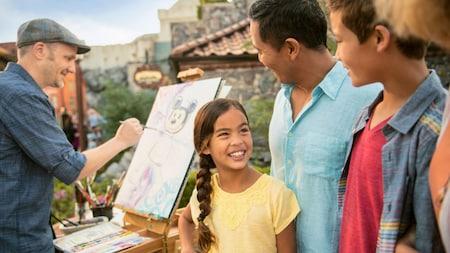 Una familia sonríe mientras mira a un hombre pintando una figura de Mickey Mouse