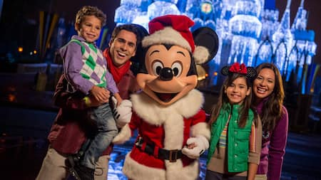 Mickey dressed as Santa poses for a picture with a family in front of Cinderella Castle decorated in lights.