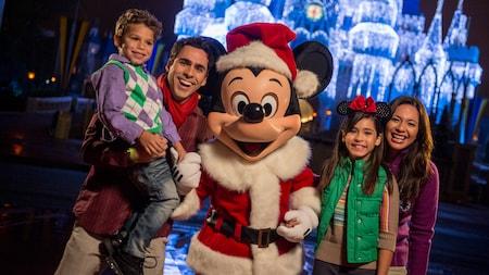 Mickey vestido de Santa Claus posa para una foto con una familia frente a Cinderella Castle decorado con luces.