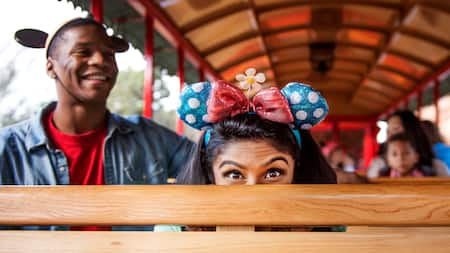 A Guest wearing Minnie Mouse headgear playfully ducks down behind a seat on a tram ride