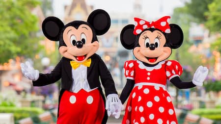 Mickey Mouse and Minnie Mouse pose, holding hands
