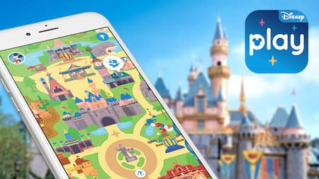 Image of a phone using the Play Disney Parks App in front of Sleeping Beauty Castle