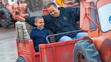 A man and a boy ride a tractor
