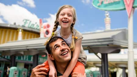 A smiling girl rides on a man's shoulders near Flos V8 Cafe