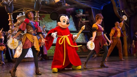 Performers dance on a stage next to Sorcerer Mickey