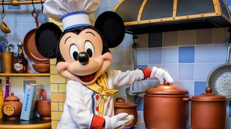 Dressed in chef whites, Mickey Mouse prepares to take the lid off a pot on a stove