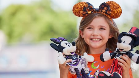 A girl with a Mickey and Minnie doll at Disneyland Resort during Halloween Time