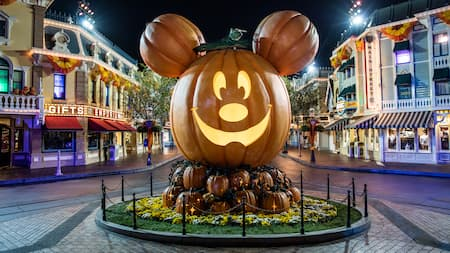 A giant replica jack o lantern with Mickey Mouse's face and 2 pumpkins for ears in a display at one end of Main Street U S A at Disneyland Park