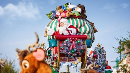 Santa Claus waves from his sleigh as a giant bag of plush toys balances behind him