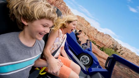 A mother and son take a tight turn on the Radiator Springs Racers track