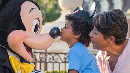 A small boy gives Mickey Mouse a kiss on the nose while his grandmother watches
