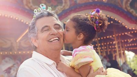 El Prince Charming Regal Carrousel da vueltas mientras una niña besa a su abuelo en la mejilla