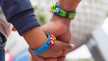 Abuelo y nieto de la mano, con coloridas MagicBands temáticas de Disney en la muñeca