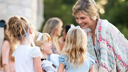2Las niñas y su abuela sonríen en los espacios al aire libre Cinderella en un Walt Disney Resort