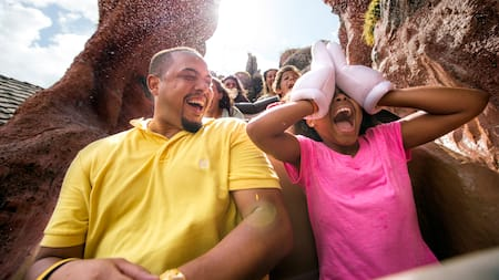 A young girl wearing Mickey gloves covers her eyes as she rides Splash Mountain with her father