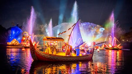 A man bedecked in ancient Asian attire rides on a sailing vessel with hanging lanterns amid erupting fountains