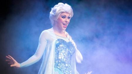 La reina Elsa canta en el escenario, rodeada de neblina glacial