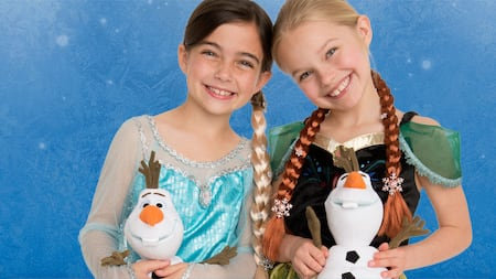 Two little girls, dressed as Anna and Elsa, each holding a plush Olaf toy