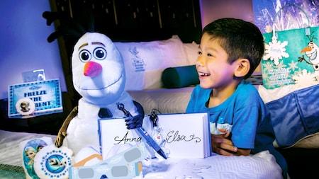 Un niño mira sus regalos de Frozen, incluidos un muñeco de peluche de Olaf y un libro de autógrafos firmado por Anna y Elsa