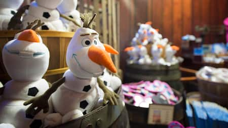 Un barril en una tienda lleno con peluches de Olaf de la película animada de Disney, Frozen