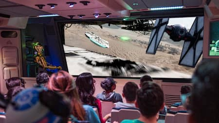 A seated audience watches imagery on a screen depicting an aerial chase in which a TIE fighter pursues and fires blasters at the Millennium Falcon
