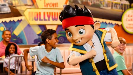 A young boy dances with Jake during a Disney Play n Dine experience