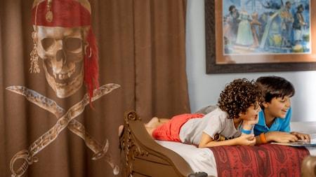 Dos niños leen juntos una historia acostados boca abajo en un barco con forma de cama dentro de una habitación con temática de piratas en Disney's Caribbean Beach Resort