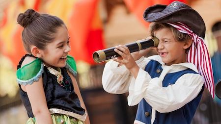 Una niña vestida como Anna de 'Frozen' se ríe mientras su hermano vestido como pirata mira a través de un catalejo