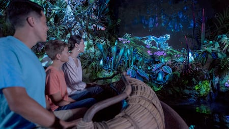 A mother, son and father watch in wonder as Pandoran animals spring to life on Na'vi River Journey