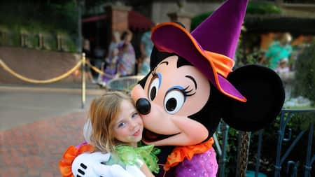 Minnie Mouse wears a witch costume and hugs a little girl in a Tinker Bell costume