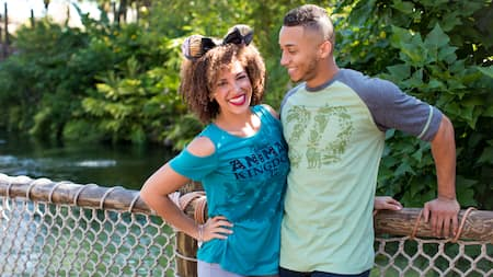 2 Guests stand on a bridge at Disney's Animal Kingdom Theme Park wearing 20th anniversary apparel and accessories