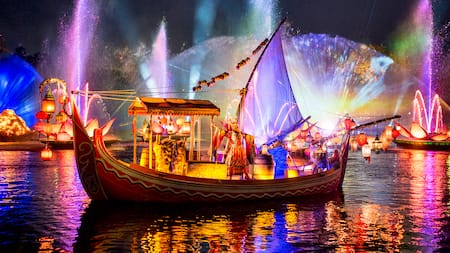 A storyteller dressed in a traditional Asian costume stands on a boat during a light show over a lake