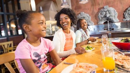 Família feliz saboreia uma pizza e outro prato italiano no Via Napoli Ristorante e Pizzeria