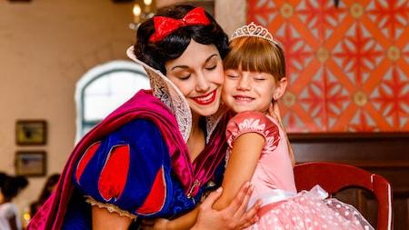 Snow White abraçando uma menina que está usando um vestido de princesa e uma coroa, sentada ao seu lado