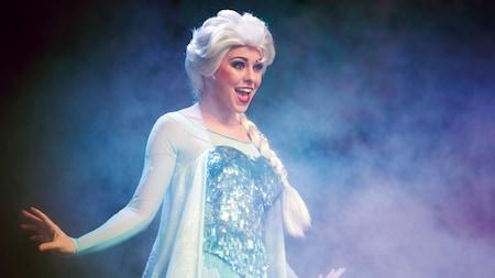 Elsa se apresenta em um palco enevoado durante a For the First Time in Forever: A Frozen Sing-Along Celebration