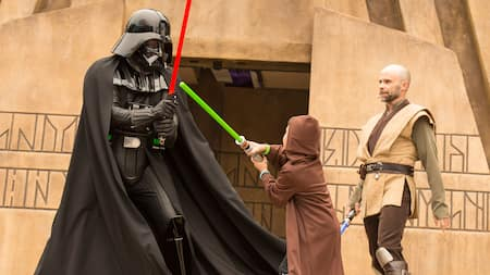 A young Guest engaging in a lightsaber battle with Darth Vader at Jedi Training: Trails of the Temple