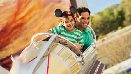 A father and his son smile while riding aboard Astro Orbiter in Tomorrowland at Magic Kingdom park