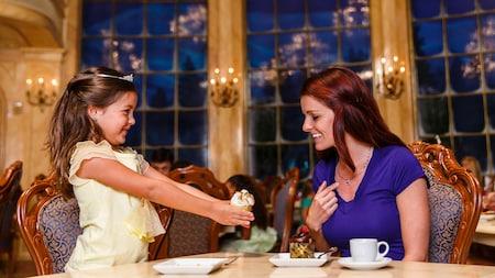Uma jovem Visitante com uma tiara segura um cupcake durante uma experiência de refeição no Be Our Guest Restaurant