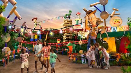 Una familia pasea felizmente por Toy Story Land mientras un grupo de amigos posa para una selfi cerca de Woody