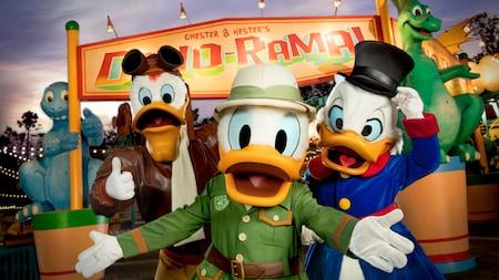 """Launchpad McQuack, Donald Duck e Scrooge McDuck posam em frente a estátuas de dinossauros e uma placa em que se lê """"Chester and Hester's Dino-Rama"""""""