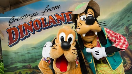 Goofy and Pluto stand in front of a giant postcard that reads, Greetings from DinoLand USA