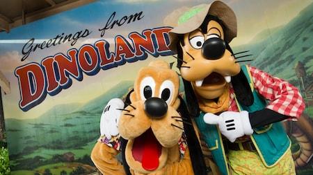 Goofy y Pluto están parados frente a una postal gigante que dice: Saludos desde DinoLand, U.S.A.