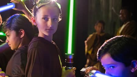 Three young Jedi holding lightsabers