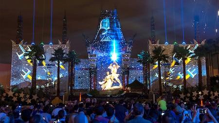 Um teatro exibe projeções de Luke Skywalker, Princesa Leia, Darth Vader e caças estelares Xwing perto de árvores e do público