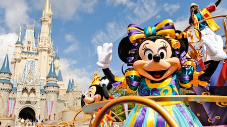 Minnie Mouse saluda desde una carroza frente a Cinderella Castle