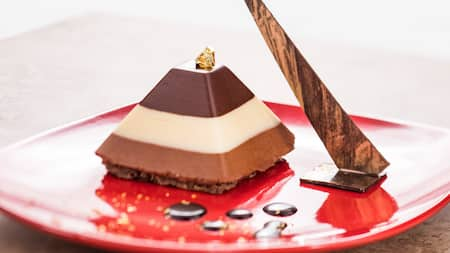 A chocolate pyramid on plate near a chocolate sculpture