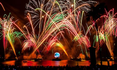 Fireworks burst in the sky near fountains, a body of water and a crowd of onlookers