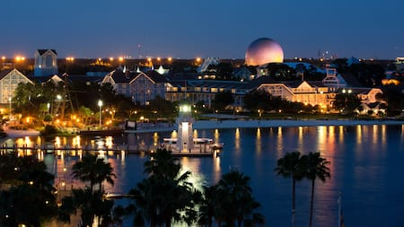 A light house in a lake near palm trees, a resort and Spaceship Earth