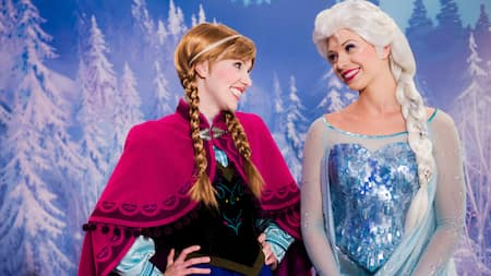 Frozen characters Anna and Elsa smile at one another