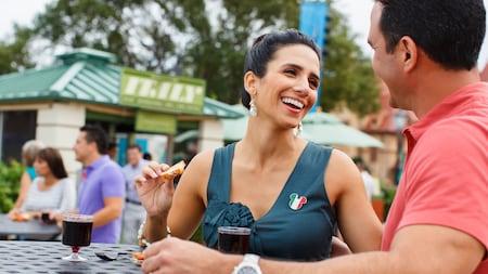 Un hombre y una mujer se sonríen el uno al otro mientras prueban comidas y vino en el pabellón de Italia
